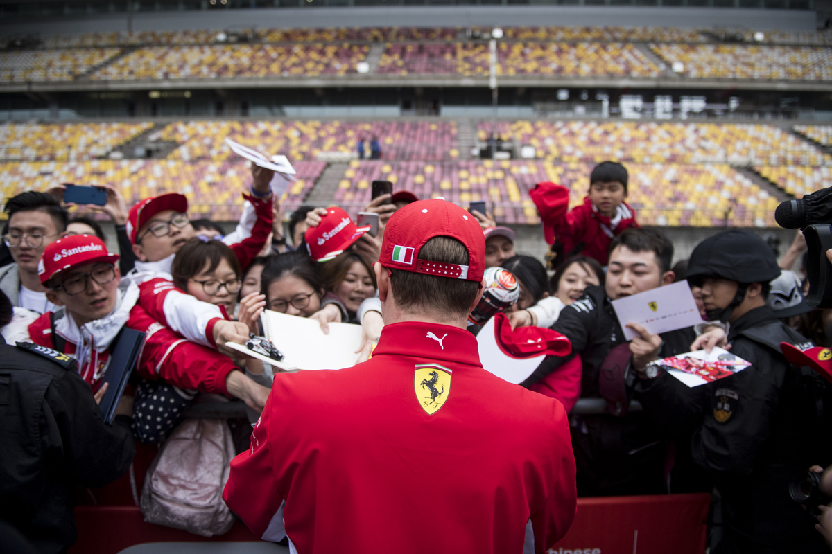 Ferrari's Finnish driver Kimi Raikkonen (C) signs autographs prior to the Formula One Chinese Grand Prix in Shanghai on April 12, 2018.  / AFP PHOTO / Johannes EISELE