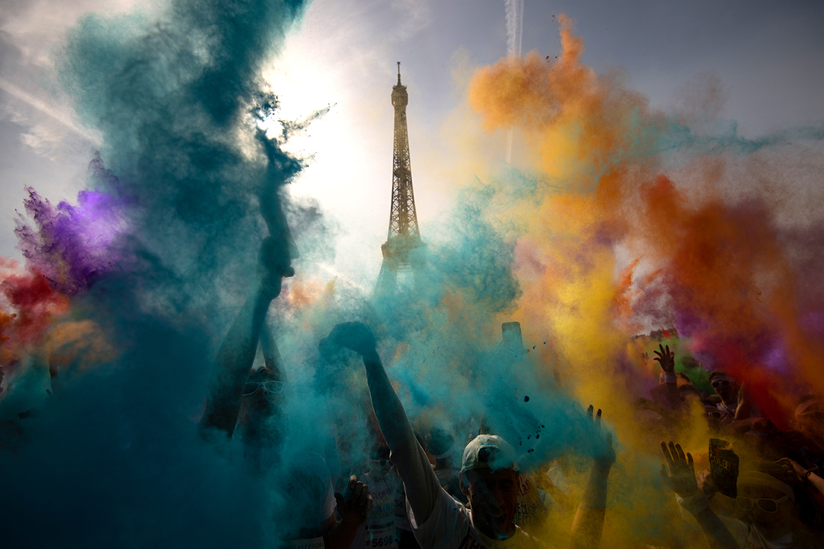 Runners celebrate under coloured powder finishing their five kilometers in the Color Run 2018 at the Eiffel Tower in Paris on April 15, 2018.Runners are showered with coloured powder at stations along the way in the five kilometres Color Run in which participant are all equal, no winners nor prizes for the finishers. / AFP PHOTO / Christophe SIMON