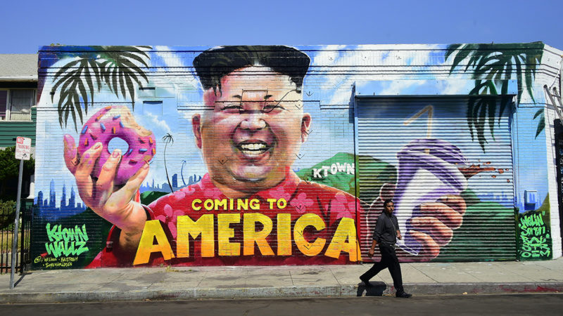 A pedestrian walks past a mural titled 'Coming To America' depicting North Korean leader Kim Jong-un holding a donut and milkshake by graffiti artsists @welinoo, @balstroem and @sorenarildsen in Los Angeles, California on May 14, 2018, created as part of the Ktown Wallz Project in the city's Koreatown neighborhod.US President Donald Trump is scheduled to meet with North Korean leader Kim Jong Un on June 12, 2018 in Singapore.   / AFP PHOTO / Frederic J. BROWN / RESTRICTED TO EDITORIAL USE - MANDATORY MENTION OF THE ARTIST UPON PUBLICATION - TO ILLUSTRATE THE EVENT AS SPECIFIED IN THE CAPTION