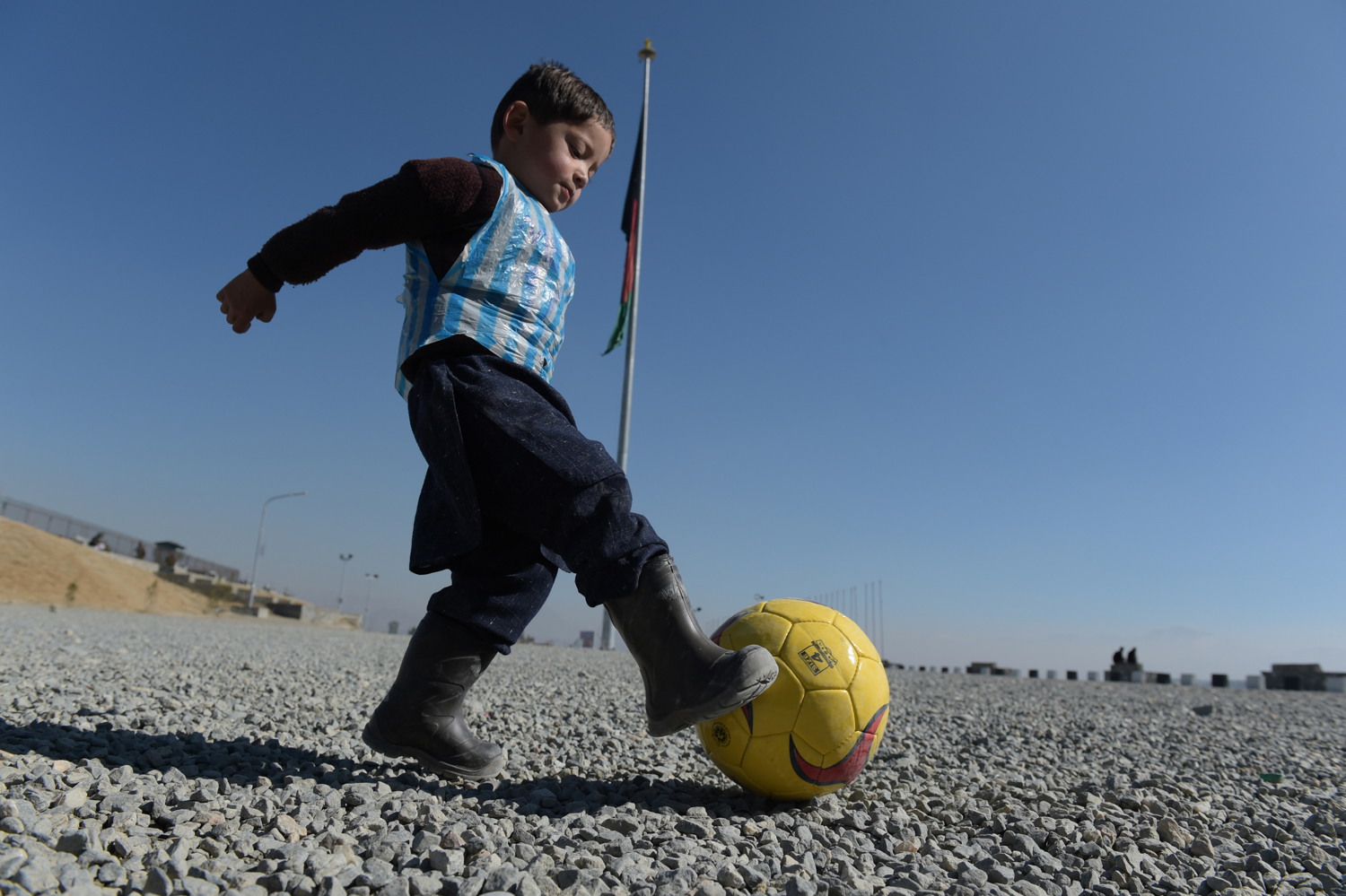 Afghan boy five-year-old Murtaza Ahmadi, a young Lionel Messi fan, plays football in Kabul on February 1, 2016. Barcelona star Lionel Messi is hoping to arrange a meeting with an Afghan boy who shot to fame after pictures of him dressed in a striped plastic bag jersey went viral, Kabul's football federation said on February 1. AFP PHOTO / SHAH Marai / AFP PHOTO / SHAH MARAIAz ötéves Lionel Messi rajongó  Murtaza Ahmadi zacskókból készült mezében focizik KabulbanFotó: Shah Marai / AFP