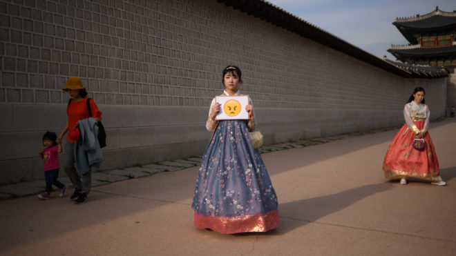 """Student Kim Dan-bi (24) poses for a photo holding an emoji after being asked to chose one that she felt best represented her feelings following US President Donald Trump's abrupt decision to cancel a summit with North Korean leader Kim Jong Un, at Gyeongbokgung palace in central Seoul on May 25, 2018.North Korea said on May 25 it is willing to talk to the United States """"at any time"""" after President Donald Trump abruptly cancelled a summit, prompting China to urge both sides to show restraint as a pall of uncertainty settled over the turbulent Korean peninsula once more. / AFP PHOTO / Ed JONES"""