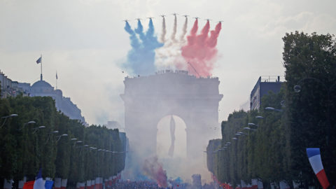 The Patrouille de France jets, trailling smoke in the colours of the national flag, fly over the Champs Elysee avenue and the Arch of Triumph (Arc de Triomphe) as supporters welcome players of the French national football team after they won the Russia 2018 World Cup final football match on July 16, 2018 in Paris. / AFP PHOTO / CHARLY TRIBALLEAU