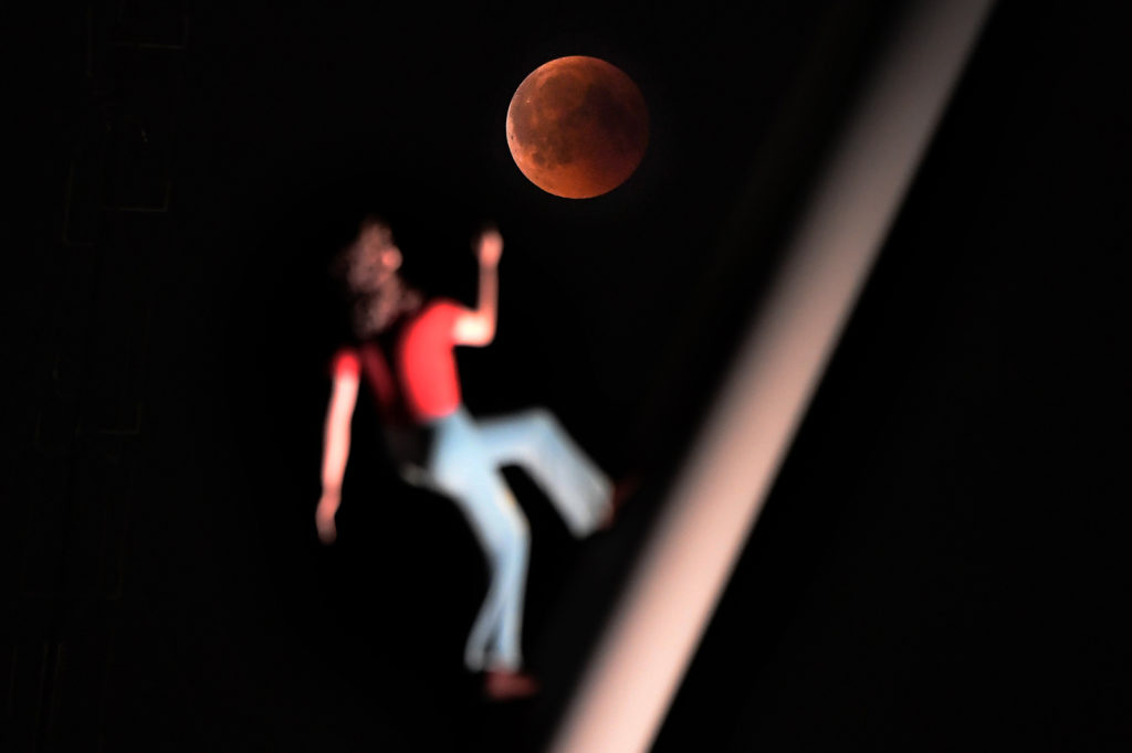 """A """"blood moon"""" eclipse is pictured with a sculpture by the American artist Jonathan Borofsky """"Woman walking to the sky"""" on July 27, 2018 in Strasbourg, eastern France. The celestial show is the result of the sun, Earth, and Moon lining up perfectly for a lunar eclipse just as the Moon is near its closest orbit point to Earth, making it appear """"super"""" large. / AFP PHOTO / FREDERICK FLORIN"""