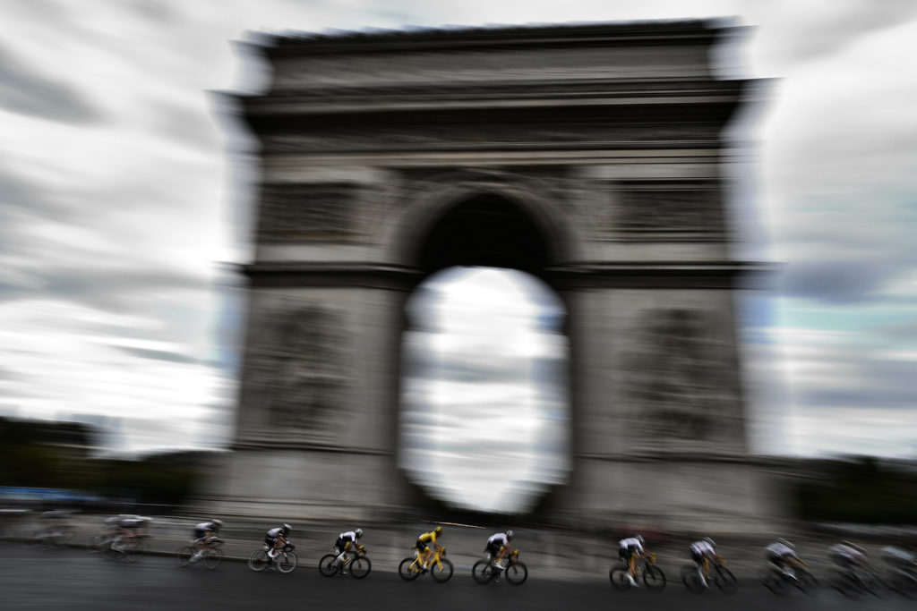 Great Britain's Geraint Thomas (C) wearing the overall leader's yellow jersey rides  past the Arc de triomphe monument during the 21st and last stage of the 105th edition of the Tour de France cycling race between Houilles and Paris Champs-Elysees, on July 29, 2018. / AFP PHOTO / Jeff PACHOUD