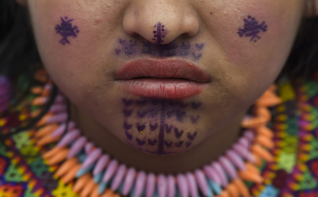 """A Colombian Embera indigenous woman, who was displaced by the armed conflict and resettled in the city, attends a gathering called """"La Gran Minga"""", at the Bolivar square in Bogota, on July 29, 2018.The """"Minga"""" -an indigenous concept referring to solidarity among a community- aims at integrating the Embera indigenous people into society and raising awareness of the reality they live. / AFP PHOTO / Raul ARBOLEDA"""