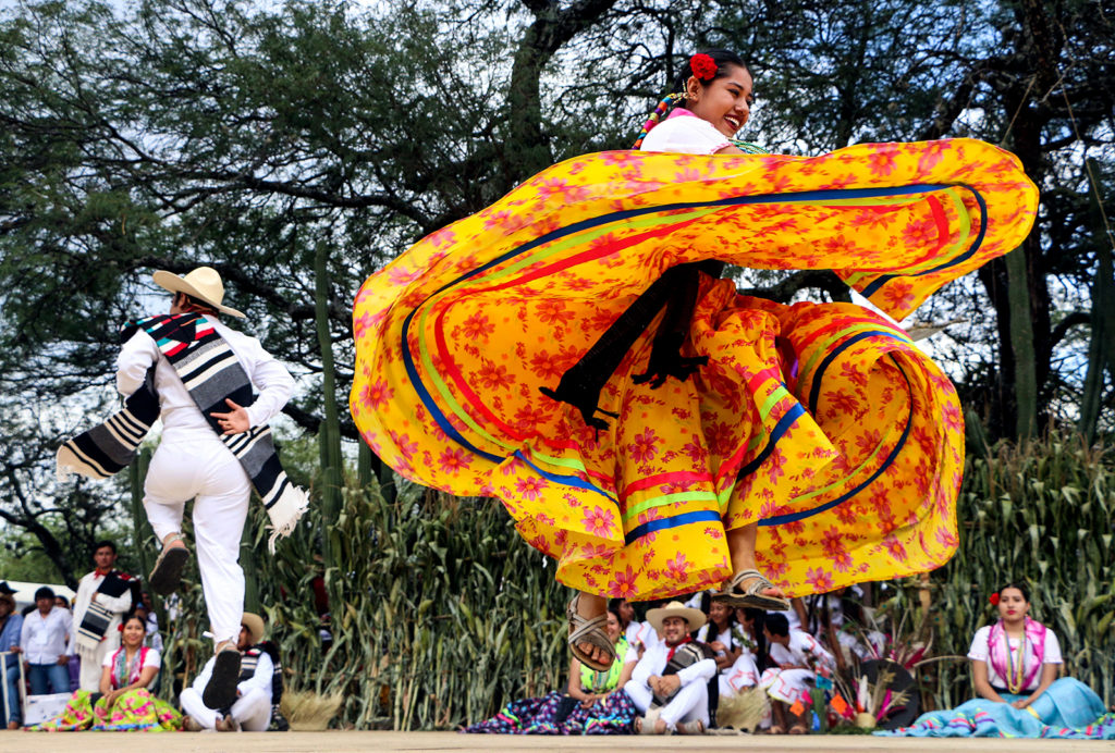 Regional dancers perform at the Guelaguetza festival on July 30, 2018 in Zaachila, Oaxaca, Mexico. The Guelaguetza is a festival held once a year which gathers music, dance, gastronomy and handicrafts of different ethnic groups and tribes of the state of Oaxaca. / AFP PHOTO / PATRICIA CASTELLANOS