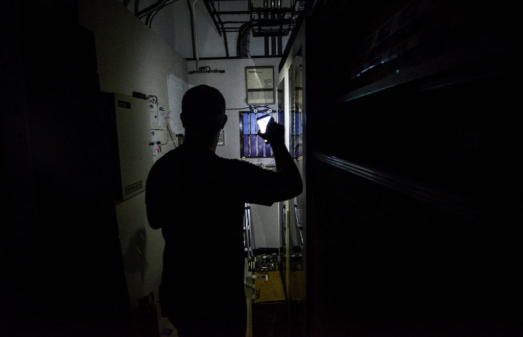 A man uses his cell phone as a flashlight at his workplace, during a power cut in Caracas on July 31, 2018A power failure cut electricity to 80 percent of the Venezuelan capital Caracas Tuesday, provoking transport and communications chaos, authorities said. / AFP PHOTO / Juan BARRETO