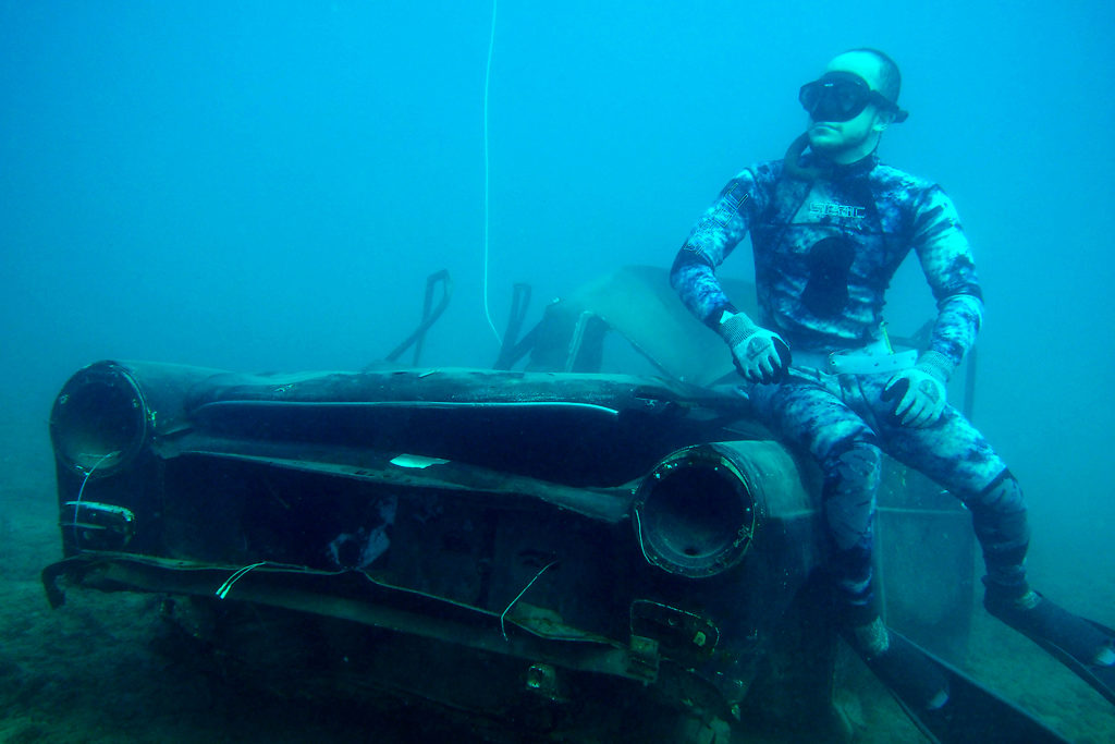 A diver poses for a photograph next to an immersed car off the coast of the southern Lebanese port city of Sidon on August 1, 2018.Environmental activists on July 28 dropped off old battle tanks provided by the Lebanese Armed Forces as well as other vehicles into the Mediterranean Sea, about three kilometres off the coast of the southern Lebanese port city of Sidon to create new habitat for marine life. / AFP PHOTO / IBRAHIM CHALHOUB