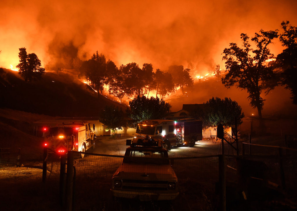 Firefighters conduct a controlled burn to defend houses against flames from the Ranch fire, as it continues to spreads towards the town of Upper Lake, California on August 2, 2018.Thousands of firefighters in California made some progress against several large-scale blazes that have turned around 200,000 acres (80,940 hectares) into an ashen wasteland, destroyed expensive homes, and killed eight fire personnel and civilians in the most populous US state. / AFP PHOTO / Mark RALSTON