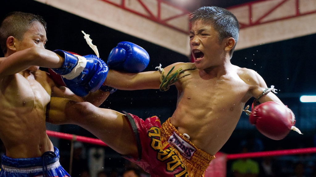 (FILES) This file photo taken on June 28, 2012 shows young Muay Thai boxers fighting in the ring at a boxing stadium in Buriram province. - Thousands of child boxers compete in Thailand's traditional martial art with dreams of belts, glory and prize money -- but the death of a 13-year-old on November 10 has lit up a sensitive debate over whether competitors start too young. (Photo by Nicolas ASFOURI / AFP)