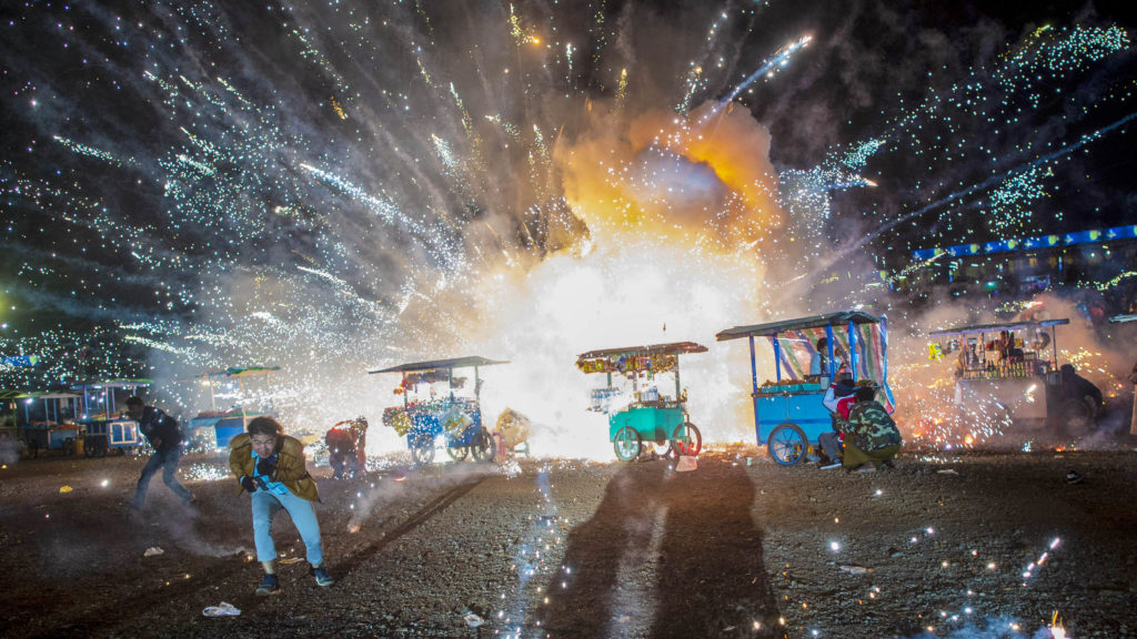 This picture taken on November 15, 2018 shows some revellers running away from exploding fireworks from a hot-air ballon during the Tazaungdaing Lighting Festival at Taunggyi in Myanmar's northeastern Shan State. - Brightly coloured balloons with hundreds of homemade fireworks woven into their frames are sent soaring into the night sky, showering down cascades of sparks onto adoring crowds in the annual Taunggyi fire balloon festival. (Photo by Ye Aung Thu / AFP)