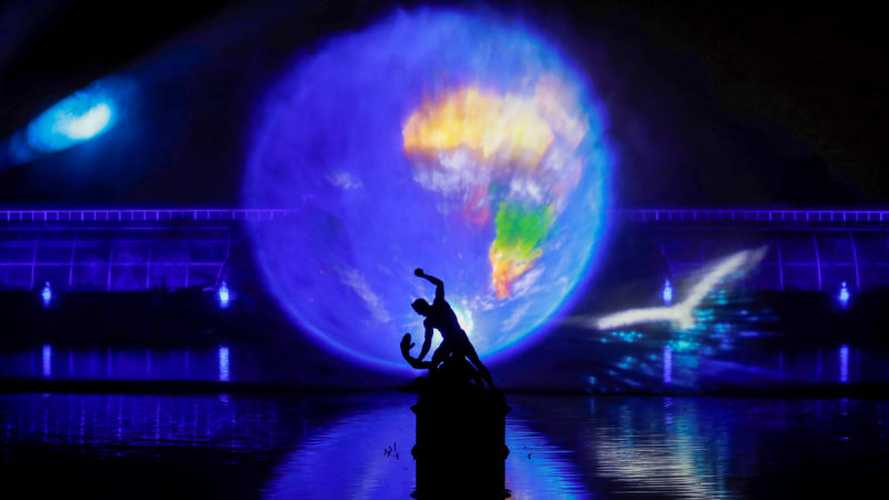 """Laser beams create images projected onto a sheet of water sprayed into the air in front of the Palm House, during a photocall at Kew Gardens in south west London, on November 21, 2018, during an event to promote the launch of the """"Christmas at Kew Gardens"""" event. - The Kew at Night Christmas trail is illuminated with numerous art installations especially commissioned. (Photo by Tolga AKMEN / AFP)"""