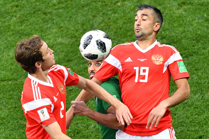 Russia's defender Mario Fernandes (L) and midfielder Alexander Samedov compete for the ball with Saudi Arabia's forward Salem Al-Dawsari (C) during the Russia 2018 World Cup Group A football match between Russia and Saudi Arabia at the Luzhniki Stadium in Moscow on June 14, 2018. / AFP PHOTO / Mladen ANTONOV / RESTRICTED TO EDITORIAL USE - NO MOBILE PUSH ALERTS/DOWNLOADS