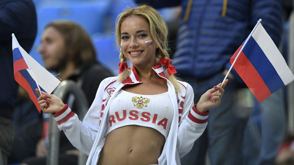 A Russia fan waves flags prior to the Russia 2018 World Cup Group A football match between Russia and Egypt at the Saint Petersburg Stadium in Saint Petersburg on June 19, 2018.  / AFP PHOTO / GABRIEL BOUYS / RESTRICTED TO EDITORIAL USE - NO MOBILE PUSH ALERTS/DOWNLOADS