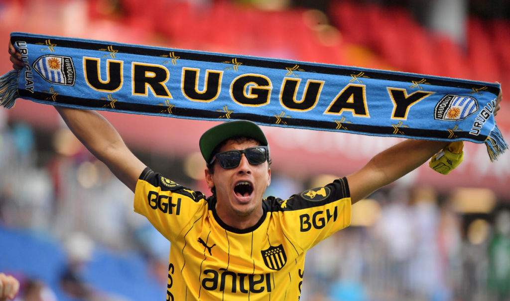 A Uruguay fan cheers with a scarf ahead of kick off of the Russia 2018 World Cup Group A football match between Uruguay and Saudi Arabia at the Rostov Arena in Rostov-On-Don on June 20, 2018. / AFP PHOTO / Pascal GUYOT / RESTRICTED TO EDITORIAL USE - NO MOBILE PUSH ALERTS/DOWNLOADS