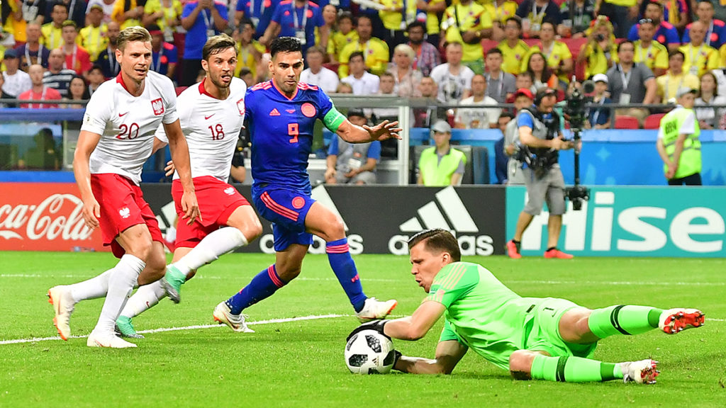 Poland's goalkeeper Wojciech Szczesny (R) stops a ball past (FromL) Poland's defender Lukasz Piszczek, Poland's defender Bartosz Bereszynski and Colombia's forward Falcao during the Russia 2018 World Cup Group H football match between Poland and Colombia at the Kazan Arena in Kazan on June 24, 2018. / AFP PHOTO / Luis Acosta / RESTRICTED TO EDITORIAL USE - NO MOBILE PUSH ALERTS/DOWNLOADS