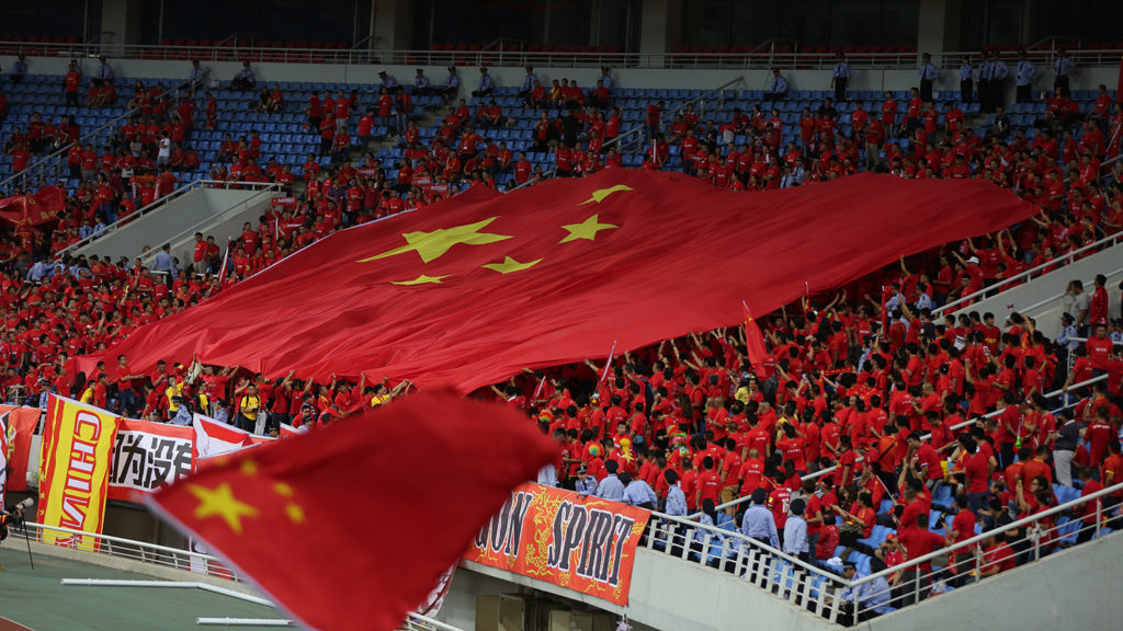 """Chinese football fans pass on a giant national flag to show support for the China team during a Group A soccer match between China and Iran of the FIFA World Cup 2018 Asian Qualifiers Final in Shenyang city, northeast China's Liaoning province, 6 September 2016.Despite massive recent investment in the game domestically and abroad, China's hopes of qualification for the 2018 World Cup could be dented significantly if the team loses at home to Iran. A 2-3 loss in South Korea in the opening game of the final round of Asian qualification last week means that a defeat in Shenyang could potentially leave China six points adrift of the top two spots in Group A that offer automatic progress to Russia in 2018. With more than US$400 million spent by Chinese Super League clubs in 2016 on famous foreign players as well as a state-run youth development program gathering pace, there has been growing optimism for the future of the game in the world's most populated country in the long-term. In the short-term, however, much depends on a victory against a tough Iran team — even so early in qualifying. China was trailing South Korea 0-3 with 20 minutes remaining but goals from Yu Hai and Hao Junmin forced the 2002 World Cup semifinalists to hang on for the final whistle. And coach Gao Hongbo wants his China team to continue where it left off in Seoul. """"If we can play against Iran with the same spirit as the last part of the last game then we can get a good result,"""" he said. """"There are nine games remaining in the group and this is our first home game. """"We need to do well in front of our own fans if we are going to achieve our goal of qualifying for the World Cup."""""""