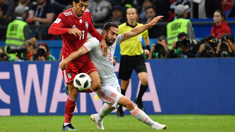 Iran's forward Vahid Amiri (L) vies for the ball with Spain's defender Dani Carvajal during the Russia 2018 World Cup Group B football match between Iran and Spain at the Kazan Arena in Kazan on June 20, 2018. / AFP PHOTO / SAEED KHAN / RESTRICTED TO EDITORIAL USE - NO MOBILE PUSH ALERTS/DOWNLOADS