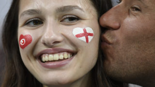 Two fans share a kiss before the Russia 2018 World Cup Group G football match between Tunisia and England at the Volgograd Arena in Volgograd on June 18, 2018. / AFP PHOTO / Philippe DESMAZES / RESTRICTED TO EDITORIAL USE - NO MOBILE PUSH ALERTS/DOWNLOADS