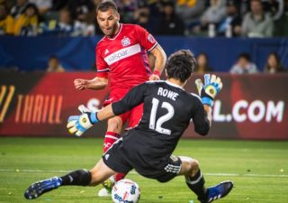 CARSON, CA - MAY 6: Nemanja Nikolic #23 of Chicago Fire scores a goal as Brian Rowe #12 of Los Angeles Galaxy defends during Los Angeles Galaxy's MLS match against Chicago Fire at the StubHub Center on May 6, 2017 in Carson, California.  The match ended in a 2-2 tie.(Photo by Shaun Clark/Getty Images) *** Local Caption *** Nemanja Nikolic; Brian Rowe