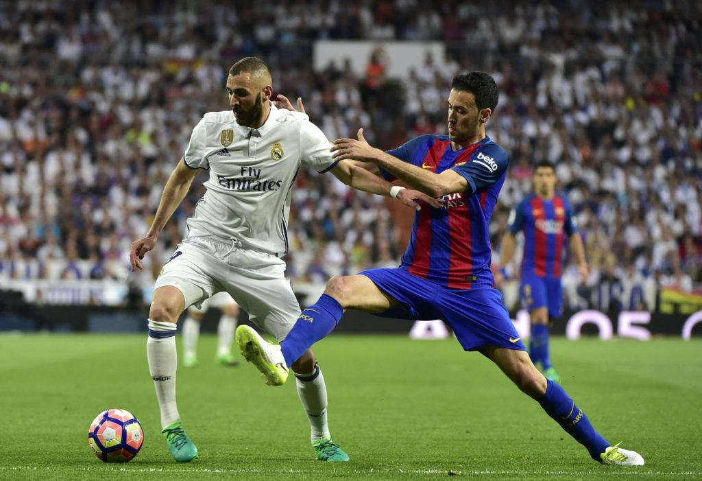 Real Madrid's French forward Karim Benzema (L) vies with Barcelona's midfielder Sergio Busquets (R) during the Spanish league football match Real Madrid CF vs FC Barcelona at the Santiago Bernabeu stadium in Madrid on April 23, 2017. / AFP PHOTO / GERARD JULIEN