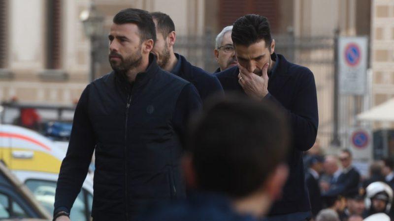 Juventus players Juventus' Giorgio Chiellini (hidden), Gianluigi Buffon (R) and Andrea Barzagli arrive at the funeral of Fiorentina's captain Davide Astori on March 8, 2018 in Florence. Italian player Davide Astori likely died from a cardiac arrest linked to the slowing of his heart rate following the initial results of his autopsy.  Fiorentina and Astori's former club Cagliari announced they will retire his number 13 shirt in honour of the 31-year-old Italy international, who was found dead in his hotel room on Sunday ahead of a Serie A match at Udinese. / AFP PHOTO / Filippo MONTEFORTE