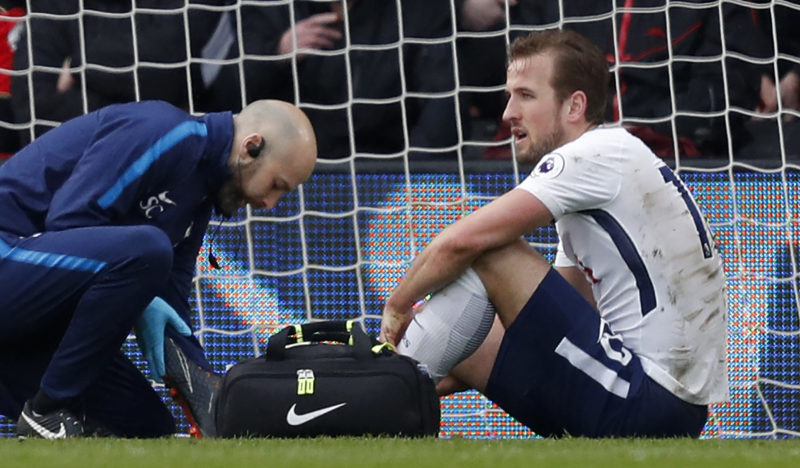 Tottenham Hotspur's English striker Harry Kane (R) receives medical attention after picking up an injury during the English Premier League football match between Bournemouth and Tottenham Hotspur at the Vitality Stadium in Bournemouth, southern England on March 11, 2018. / AFP PHOTO / Adrian DENNIS / RESTRICTED TO EDITORIAL USE. No use with unauthorized audio, video, data, fixture lists, club/league logos or 'live' services. Online in-match use limited to 75 images, no video emulation. No use in betting, games or single club/league/player publications.  /