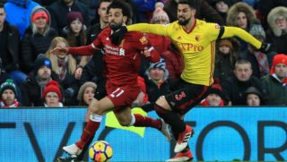 Liverpool's Egyptian midfielder Mohamed Salah (L) vies with Watford's Uruguayan defender Miguel Britos during the English Premier League football match between Liverpool and Watford at Anfield in Liverpool, north west England on March 17, 2018. / AFP PHOTO / Lindsey PARNABY / RESTRICTED TO EDITORIAL USE. No use with unauthorized audio, video, data, fixture lists, club/league logos or 'live' services. Online in-match use limited to 75 images, no video emulation. No use in betting, games or single club/league/player publications.  /