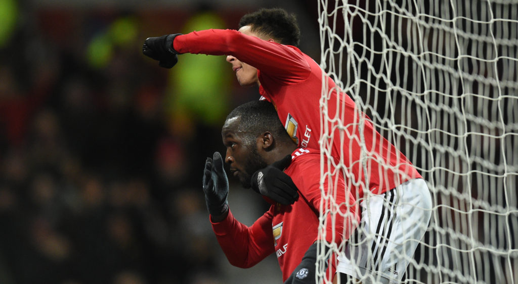 Manchester United's Belgian striker Romelu Lukaku (bottom) celebrates scoring the team's first goal with Manchester United's English midfielder Jesse Lingard during the English FA Cup quarter-final football match between Manchester United and Brighton and Hove Albion at Old Trafford in Manchester, north west England, on March 17, 2018. / AFP PHOTO / Oli SCARFF / RESTRICTED TO EDITORIAL USE. No use with unauthorized audio, video, data, fixture lists, club/league logos or 'live' services. Online in-match use limited to 75 images, no video emulation. No use in betting, games or single club/league/player publications.  /
