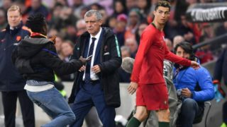 A fan runs next to Portugal's coach Fernando Santos (C) and Portugal's forward Cristiano Ronaldo during his international friendly football match between Portugal and Netherlands at Stade de Geneve stadium in Geneva on March 26, 2018. / AFP PHOTO / Fabrice COFFRINI