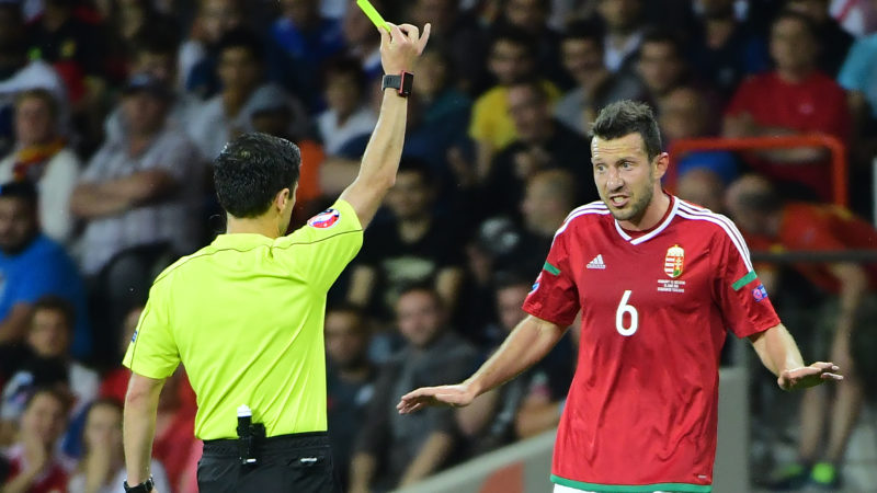 Hungary's midfielder Akos Elek (R) reacts as he receives a yellow card from Serbian referee Milorad Mazic  during the Euro 2016 round of 16 football match between Hungary and Belgium at the Stadium Municipal in Toulouse on June 26, 2016.   / AFP PHOTO / EMMANUEL DUNAND