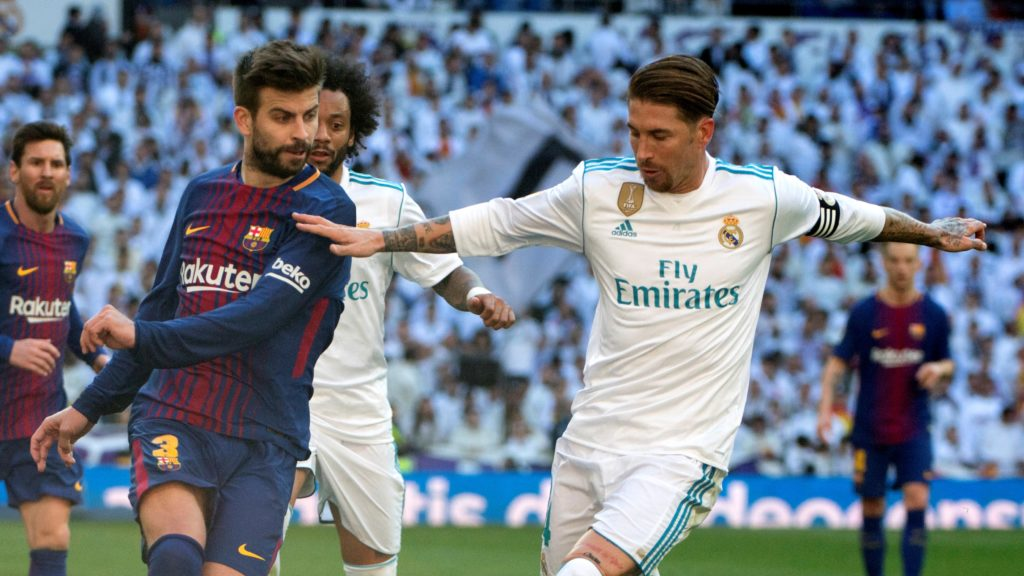 """Barcelona's Spanish defender Gerard Pique (L) vies with Real Madrid's Spanish defender Sergio Ramos during the Spanish League """"Clasico"""" football match Real Madrid CF vs FC Barcelona at the Santiago Bernabeu stadium in Madrid on December 23, 2017.  / AFP PHOTO / CURTO DE LA TORRE"""