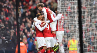 Arsenal's Gabonese striker Pierre-Emerick Aubameyang (L) celebrates, with teammates, scoring a penalty and the opening goal  during the English Premier League football match between Arsenal and Stoke City at the Emirates Stadium in London on April 1, 2018.  / AFP PHOTO / Oliver GREENWOOD / RESTRICTED TO EDITORIAL USE. No use with unauthorized audio, video, data, fixture lists, club/league logos or 'live' services. Online in-match use limited to 75 images, no video emulation. No use in betting, games or single club/league/player publications.  /