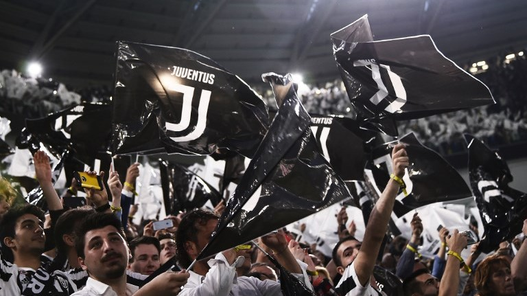 Juventus' supporters wave flags during the Italian Serie A football match between Juventus and Napoli on April 22, 2018 at the Allianz Stadium in Turin. / AFP PHOTO / MARCO BERTORELLO