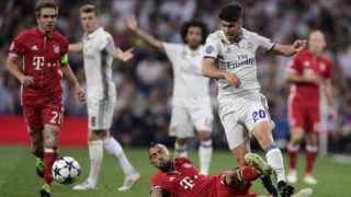 Real Madrid's midfielder Marco Asensio (R) vies with Bayern Munich's Chilean midfielder Arturo Vidal (bottom) during the UEFA Champions League quarter-final second leg football match Real Madrid vs FC Bayern Munich at the Santiago Bernabeu stadium in Madrid in Madrid on April 18, 2017. / AFP PHOTO / JAVIER SORIANO