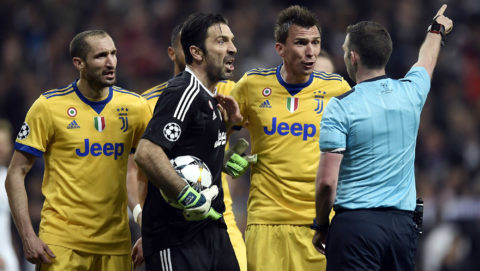 Juventus' Italian goalkeeper Gianluigi Buffon (2L) argues with the referee during the UEFA Champions League quarter-final second leg football match between Real Madrid CF and Juventus FC at the Santiago Bernabeu stadium in Madrid on April 11, 2018. / AFP PHOTO / OSCAR DEL POZO