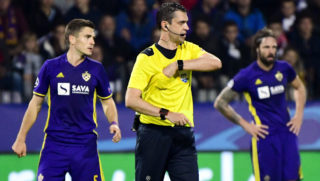 Hungarian referee Viktor Kassai (C) reacts after giving a yellow card to Maribor's Slovenian midfielder Blaz Vrhovec (L) during the UEFA Champions League group E football match between NK Maribor and Liverpool at the Ljudski vrt Stadium, in Maribor, on October 17, 2017. / AFP PHOTO / Jure MAKOVEC