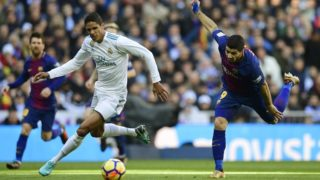 """Real Madrid's French defender Raphael Varane (L) vies with Barcelona's Uruguayan forward Luis Suarez during the Spanish League """"Clasico"""" football match Real Madrid CF vs FC Barcelona at the Santiago Bernabeu stadium in Madrid on December 23, 2017.  / AFP PHOTO / JAVIER SORIANO"""