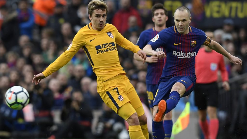 Atletico Madrid's French forward Antoine Griezmann (L) vies with Barcelona's Spanish midfielder Andres Iniesta during the Spanish league football match FC Barcelona against Club Atletico de Madrid at the Camp Nou stadium in Barcelona on March 04, 2018. / AFP PHOTO / LLUIS GENE