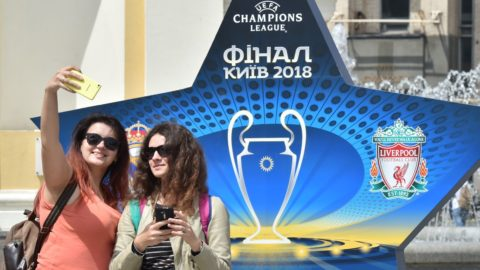 Girls make selfie in front of the official logo set on the Independence Square in the Ukrainian capital of Kiev on May 22, 2018, ahead of 2018 UEFA Champions League Final football match between Real Madrid and Liverpool FC next May 26 at the Olimpiyskiy Stadium.  / AFP PHOTO / Sergei SUPINSKY