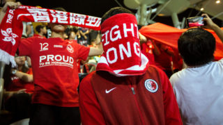 """(FILES) This file photo taken on November 9, 2017 shows a Hong Kong fan covering his face during the Chinese national anthem before an international friendly football match between Hong Kong and Bahrain at Mong Kok Stadium in Hong Kong. A Hong Kong student leader has been declared an """"enemy of the people"""" by Chinese state media for speaking out over a new law against disrespecting the national anthem, in what critics say is another attack on freedom of speech in Hong Kong. / AFP PHOTO / Isaac LAWRENCE"""