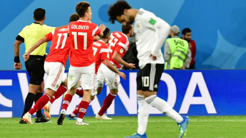 Egypt's forward Mohamed Salah reacts as Russia's forward Artem Dzyuba  celebrates with teammates after scoring during the Russia 2018 World Cup Group A football match between Russia and Egypt at the Saint Petersburg Stadium in Saint Petersburg on June 19, 2018.  / AFP PHOTO / Giuseppe CACACE / RESTRICTED TO EDITORIAL USE - NO MOBILE PUSH ALERTS/DOWNLOADS