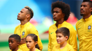 SAINT PETERSBURG, RUSSIA - JUNE 22:  Neymar and Willian of Brazil stand for the anthems prior to the 2018 FIFA World Cup Russia group E match between Brazil and Costa Rica at Saint Petersburg Stadium on June 22, 2018 in Saint Petersburg, Russia. (Photo by Robbie Jay Barratt - AMA/Getty Images)