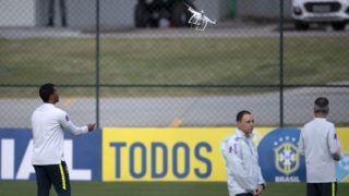A drone is guided to the ground by a Brazilian Football Confederation worker during a training session of the national football team ahead of FIFA's 2018 World Cup, at Granja Comary training centre in Teresopolis, Rio de Janeiro, Brazil, on May 24, 2018.  / AFP PHOTO / MAURO PIMENTEL