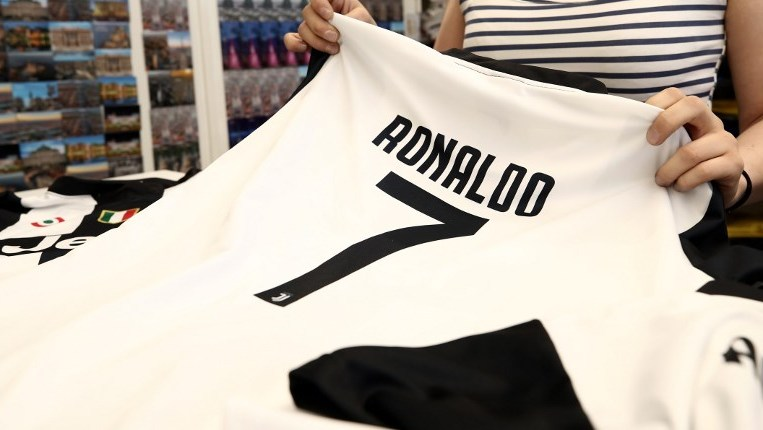 A picture taken on July 11, 2018 shows a saleswoman folding Cristiano Ronaldo's Juventus jersey in a shop in downtown Turin.  Portuguese football superstar transfer from Real Madrid to Italy's Juventus was announced on July 10.  / AFP PHOTO / Isabella Bonotto