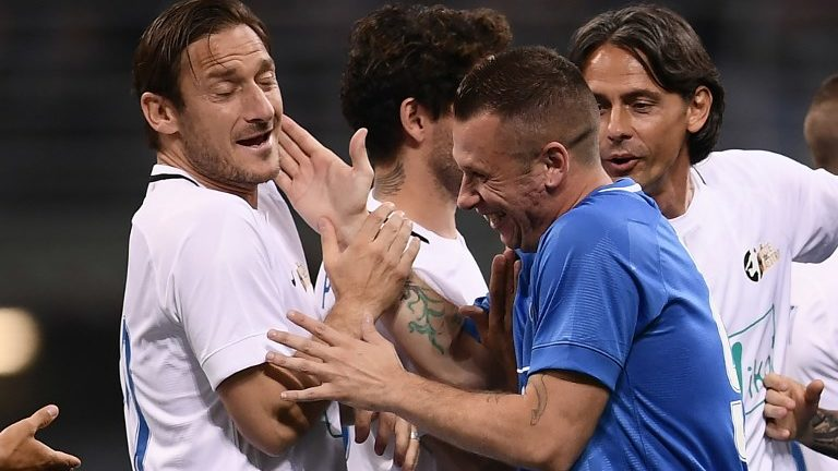 """Former Italian football players Francesco Totti (L) and Antonio Cassano joke during the """"Notte del Maestro"""" (master's night), a football match celebrating the end of former Italy's football player Andrea Pirlo's career as a football player, on May 21, 2018 at the Giuseppe Meazza Stadium in Milan.  / AFP PHOTO / MARCO BERTORELLO"""