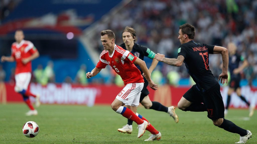 Russia's midfielder Denis Cheryshev (C) is marked by Croatia's forward Mario Mandzukic (R) during the Russia 2018 World Cup quarter-final football match between Russia and Croatia at the Fisht Stadium in Sochi on July 7, 2018. / AFP PHOTO / Adrian DENNIS / RESTRICTED TO EDITORIAL USE - NO MOBILE PUSH ALERTS/DOWNLOADS