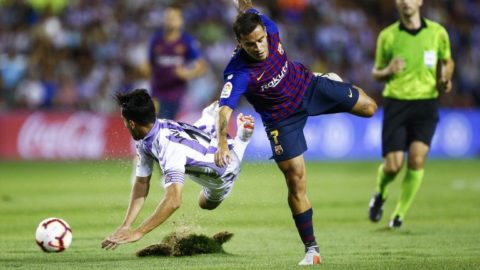 Real Valladolid's Spanish defender Javi Moyano (L) falls beside Barcelona's Brazilian midfielder Philippe Coutinho during the Spanish league football match between Real Valladolid and FC Barcelona at the Jose Zorrilla Stadium in Valladolid on August 25, 2018. / AFP PHOTO / Benjamin CREMEL