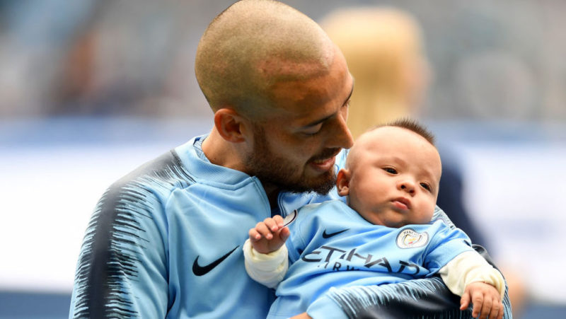 MANCHESTER, ENGLAND - AUGUST 19:  David Silva of Manchester City is seen with his son Mateo as the teams line up prior to the Premier League match between Manchester City and Huddersfield Town at Etihad Stadium on August 19, 2018 in Manchester, United Kingdom.  (Photo by Michael Regan/Getty Images)