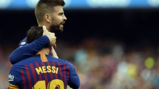 Barcelona's Spanish defender Gerard Pique (TOP) congratulates Barcelona's Argentinian forward Lionel Messi for scoring their team's opening goal during the Spanish league football match between FC Barcelona and SD Huesca at the Camp Nou stadium in Barcelona on September 2, 2018. / AFP PHOTO / LLUIS GENE